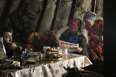 Nenets women reading an edition of 'Pravda' in a tent ('chum').