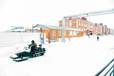 A Nenet herder riding on a snowmobile along a street in Panaevsk, a Nenets settlement in the tundra situated on the banks of the Ob River.