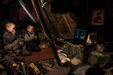 Nenets children are watching cartoon on a laptop powered by a generator which the family run for 2-3 hours each evening.