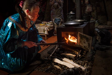Lyuba stokes the stove inside the family's tent ('chum').  There is a strict segregation of duties in a daily life of nomadic Nenets. Women maintain the fire in the stove, cook, build the tent ('chu...
