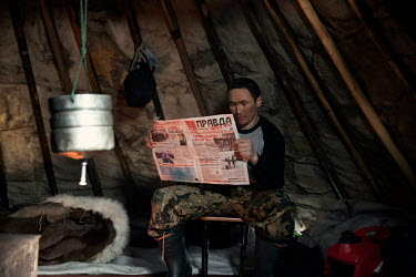 Indigenous Nenet Roman reading a copy of newspaper 'Pravda' (Truth), brought by his friend from a nearby town.