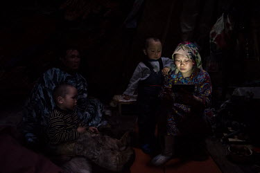Indigenous Nenets, Lyuda and Roman and their children, looking at photos and videos on their smartphone in the evening.