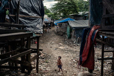 A Burmese (Myanma) child living in an informal settlement in the 'no man's land' between Myanmar and Thailand looks at Thai Army soldiers (unseen) who are looking out for illegal migrants crossing int...