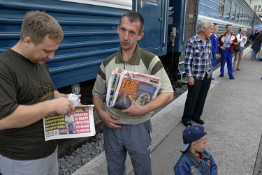 Passengers on a Trans-Siberian Express train waiting on the platform during the break in the journey.