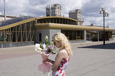 A young woman smells the bouquet of flowers she has just received flowers from a stranger near the train station. The twin towers in the background were built in 1956 in a triumphal Stalinist style.