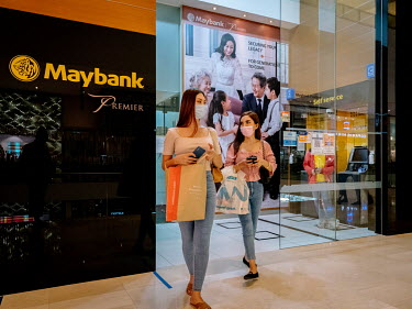 Two young women leave a Maybank ATM site in a shopping centre.