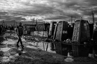 A resident walks along a muddy path next to some portable public toilets in Khayelitsha, Cape Town's largest township. Many of its 600,000 inhabitants, living in the township's most distant edges have...