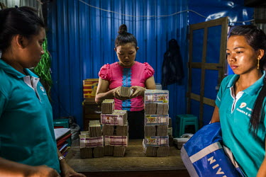 Staff count bundles of bank notes inside the Shwe Kyaung (Golden Cat) 'hundi' shop which offers cash financial services for jade traders. Traders admit that they make payments in cash for small to med...
