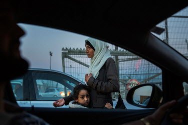 A Palestinian woman with her daughter begs as they walk between the lines of cars queuing at the Qalandia checkpoint in Ramallah in the West Bank.