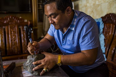 A jade trader inspects a dissected raw jade stone inside a private house. Traders like this man who has good connections within the jade market, get better information from their networks and make hom...