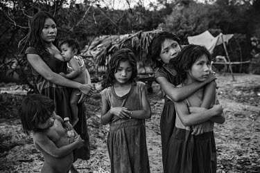 Piraha women and children, standing next to their camp on the banks of the Maici River, watch drivers passing by on the Trans-Amazonian highway hoping to be given snacks or soft drinks.