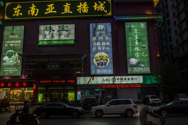 Illuminated digital advertisements, including ones for jade jewellery, above a branch of the ABC Bank located at a jade trading centre just outside the official Delong jade market.