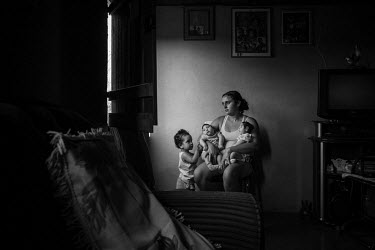 Marcela (2) gently touches one of her twin sisters, Heloa (right) and Heloisa (left) as they rest in her mother's arms at the family's home. Both babies are seven months old and both were born with mi...