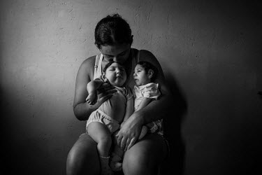 Raquel de Araujo cradles twin daughters, Heloa (right) and Heloisa (left) as they rest on her lap at the family's home. Both babies are seven months old and both were born with microcephaly caused by...
