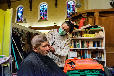 A homeless Romanian man receiving a free haircut from a volunteer at a local charity which is helping people from a church in the Paquis district.