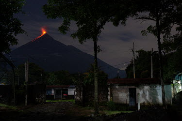 Seen from the entrance to the 15 de Octubre La Trinidad community, the Fuego Volcano, one of the most active volcanoes in the world, erupts during a period of stronger-than-usual activity.