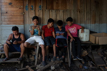 Berli Perez (left), 28, and boys from his community watch videos on their phones at the Single-Family Transitional Shelters in Escuintla City.