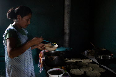 Ada Camposeco, 34, who was born in Chiapas, Mexico, while the community was there as war refugees, serves lunch for her family consisting of boiled potatoes and Chipilin leaves (Crotalaria longirostra...