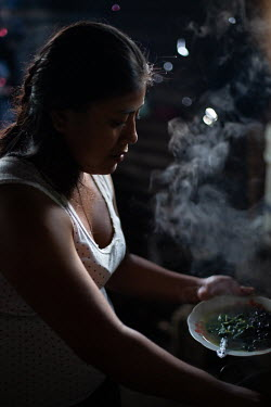 Carmen Mendez, 21, prepares to boil Chipilin leaves (Crotalaria longirostrata) known as chepil or longbeak rattlebox, for dinner, at her home in the 15 de Octubre La Trinidad community. Along with cor...