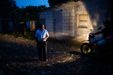 War survivor Jose Camposeco, 53, watches as two young men from the community pass him by on a motorcycle in the 15 de Octubre La Trinidad community.
