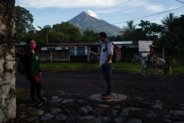 Siblings Rosaida Camposeco (left), 29, and Victalino Camposeco, 31, wait for transport at the entrance to the 15 de Octubre La Trinidad community while the Fuego Volcano looms in the background. Both...