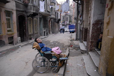 A disabled boy in a wheelchair outside in the backstreets of Tarlabashi, a poor district in the centre of Istanbul.