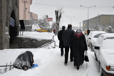 People walk past a woman sitting in the snow and begging.