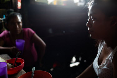 Carmen Garcia (right), 21, and her mother and war survivor Eva Garcia, 39, sit in their kitchen after dinner, at their home in the 15 de Octubre La Trinidad community. Despite fears of the constant ac...
