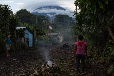 War survivor Eva Garcia (right), 39, burns rubbish and speaks with a neighbour as Fuego Volcano can be seen with some cloud coverage in the background from the 15 de Octubre La Trinidad community. Des...