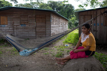 Abi Zoila Hernandez, 33, born in Chiapas, Mexico, while the community was there as war refugees, sits on a rock while her eight-month-old son Bringner sleeps in a hammock at the Single-Family Transiti...