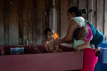 Candelaria Gomez, 32, born in Chiapas, Mexico, while the community was there as war refugees, carries her six-month-old daughter Guadalupe while she bathes her three-year-old daughter Sharon at the Si...