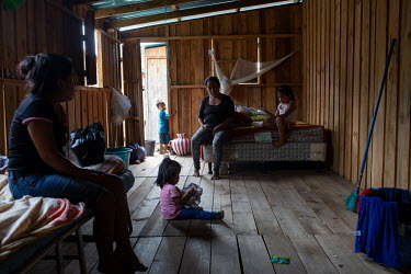 Evelyn Janeth Funes (left), 20, and her one-year-old daughter Camila (sitting on the foor), visit Evelyn's mother Gregoria Montejo, 41, and her youngest sister Adriana Funes, 6, in their unit at the S...