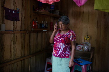 War survivor Maria Cruz Mendez, 59, speaks on the phone to her daughter inside her unit at the Single-Family Transitional Shelter. Cruz Mendez states: ''I am way too scared of the volcano to go back t...