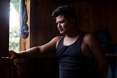 Berli Perez, 28, born in Chiapas, Mexico, while the community was there as war refugees, ponders at the window inside his Single-Family Transitional Shelter unit. A father of two boys, Berli states: '...