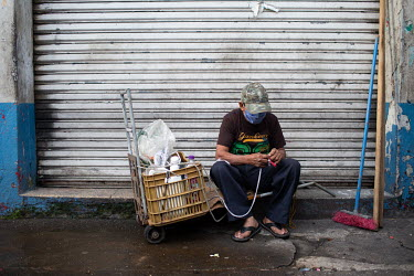 A man hauling water sits on a sidewalk to undo a knot in his rope near Escuintla City's market.
