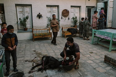 A sacrificial goat is slaughtered in the courtyard of the groom's family home as the groom arrives carrying the bride on his shoulder.
