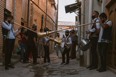 Young boys dance while men wearing embroidered waistcoats sound a drum and blow two large horns outside the groom's house to signify the beginning of the wedding ceremony as the wedding guests and nei...