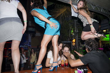 Russian and British women dancing on a nightclub's bar.