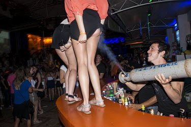 A nightclub barman blows beer gas up the skirt of a Russian girl who is dancing on the bar.