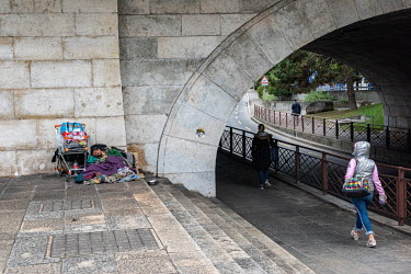 A woman passes a homeless man, sleeping by a bridge over the Rhone Riveer with his possesions in a shopping trolley.