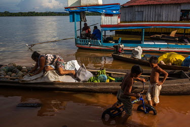Riverside dwellers unload their goods at an improvised port on the banks of the Xingu River.
