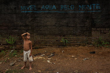 A boy stands besidea wall marked with the water level that the Xingu River is expected to reach after the construction of the Belo Monte hydroelectric dam.