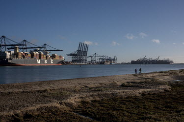 A couple walk on the beach opposite the port of Felixstowe. A combination of stockpiling for Brexit and the effects on trade of the COVID-19 crisis have meant that many ports are overloaded.