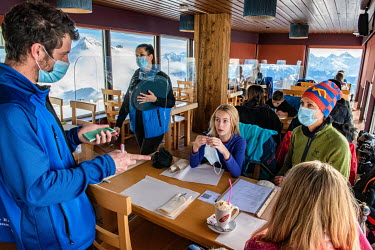 A Swedish family on a ski holiday talk to the waitor in a restaurant on the ski slopes.