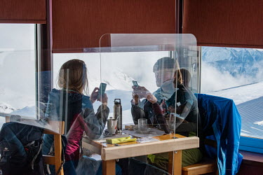 A couple sit at a table, secured by a perspex barriers, as they eat in a restaurant at the top of a ski slope which remains open but with various measures in place to try and ensure it is COVID-19 pro...
