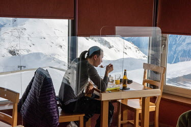 A man eats at a table, secured by a perspex barriers, in a restaurant at the top of a ski slope which remains open but with various measures inn place to try and ensure it is COVID-19 proof.