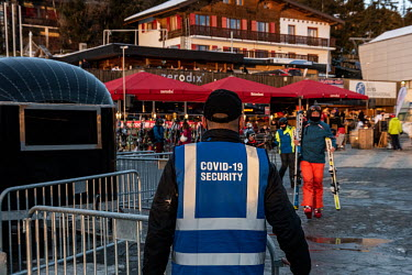 A COVID-19 security worker monitors the skiers at the bottom of the slopes.