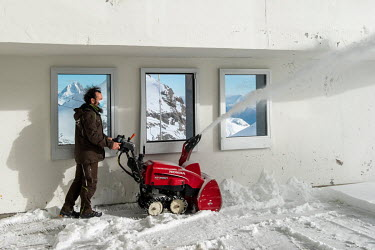 An employee clearing snow off the roof of a cable lift building at close to 3000 metres. Swiss ski stations remain open depsite the pandemic.