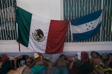 Central American migrants sleeping beneath Mexican and Honduran flags in the main square after arriving from Huixtla.