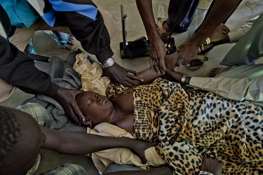 South Sudanese refugee Ajok Panchol (18) has been brought in, on stretcher to the Dzaipi transit camp health centre, by relatives. She has a fever and suspected malaria and is also pregnant.